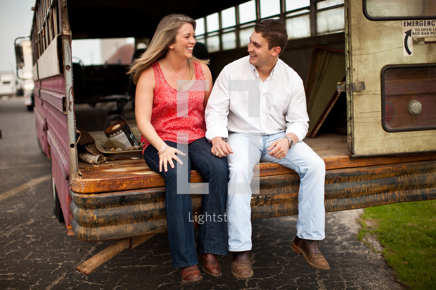 Couple sitting on back of old rusty bus in parking lot.