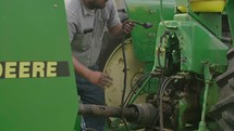 a farmer fixing a tractor