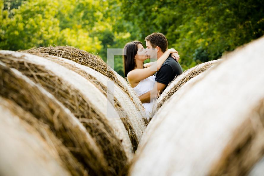 Happy couple kissing in-between hay rolls