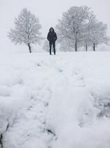 man in a coat standing in snow