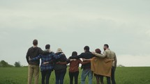 a group with arms around each other standing in a field