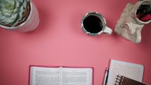 a woman reading a Bible at a pink desk