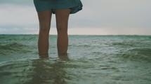 legs standing in ocean water