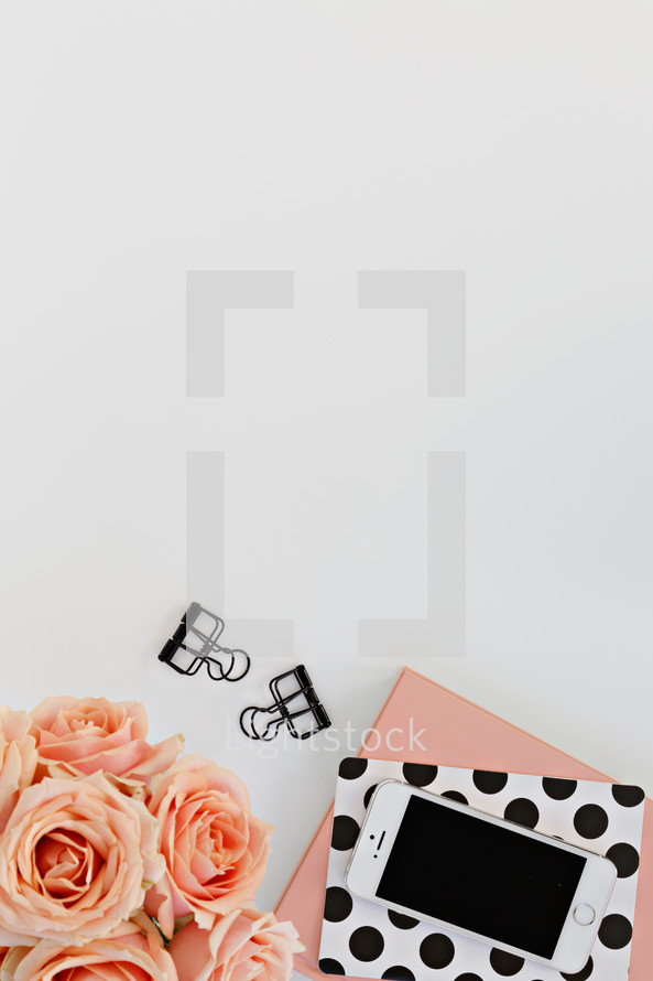 journals, peach roses, phone, and clips on a white desk