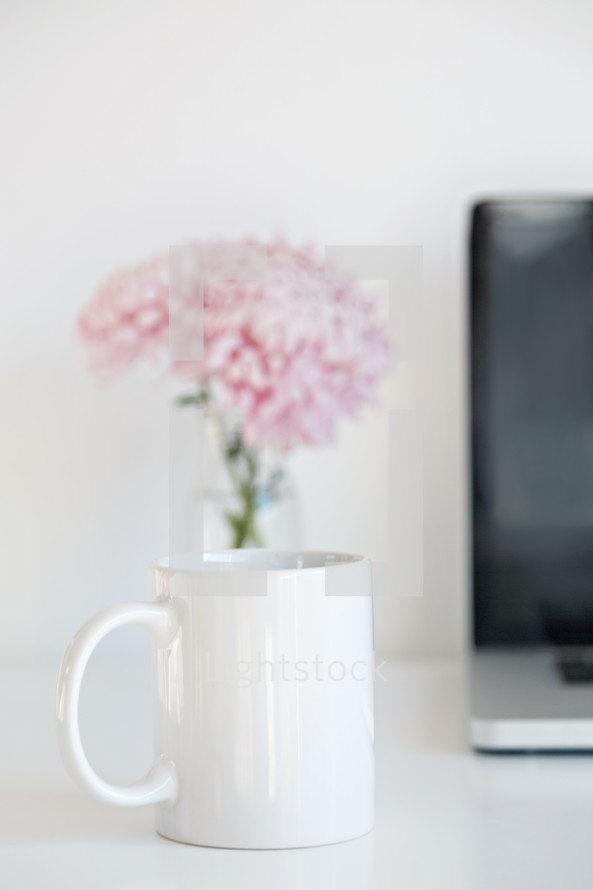 coffee cup, vase of flowers, and laptop computer on a desk