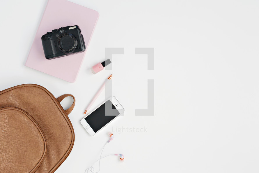leather bag, cellphone, pink notebook, nail polish, pen, earbuds, and camera