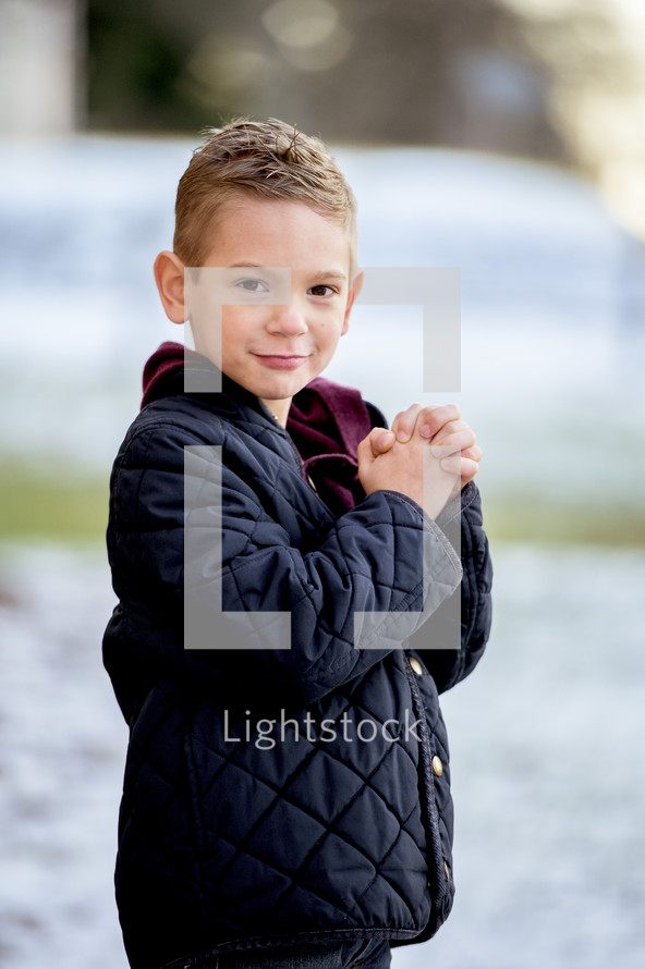 boy child praying outdoors in snow