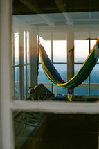 hammock on a deck overlooking fog over mountains at sunrise