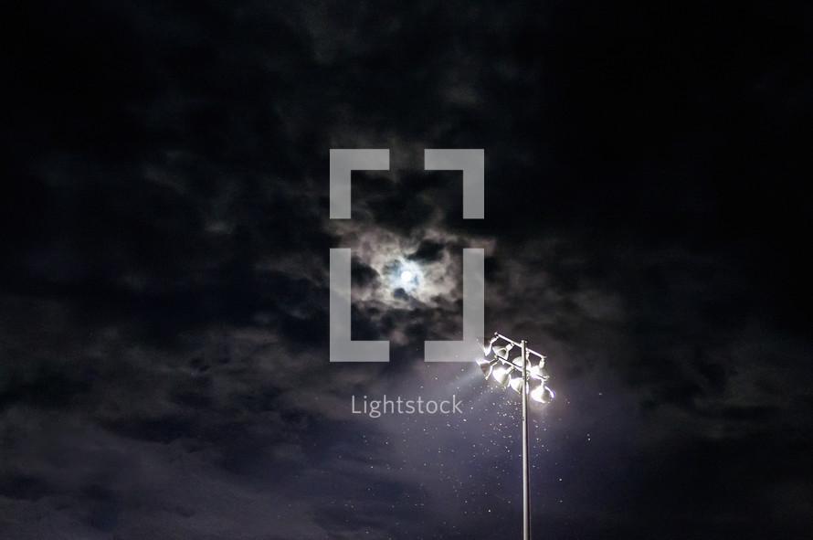 moon through clouds - ball field lights
