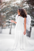 a girl dressed as an angel in the snow