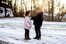 girl and boy child holding a Bible outdoors in snow