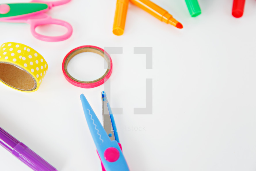 calculator, scissors, markers, and paperclips on a white background