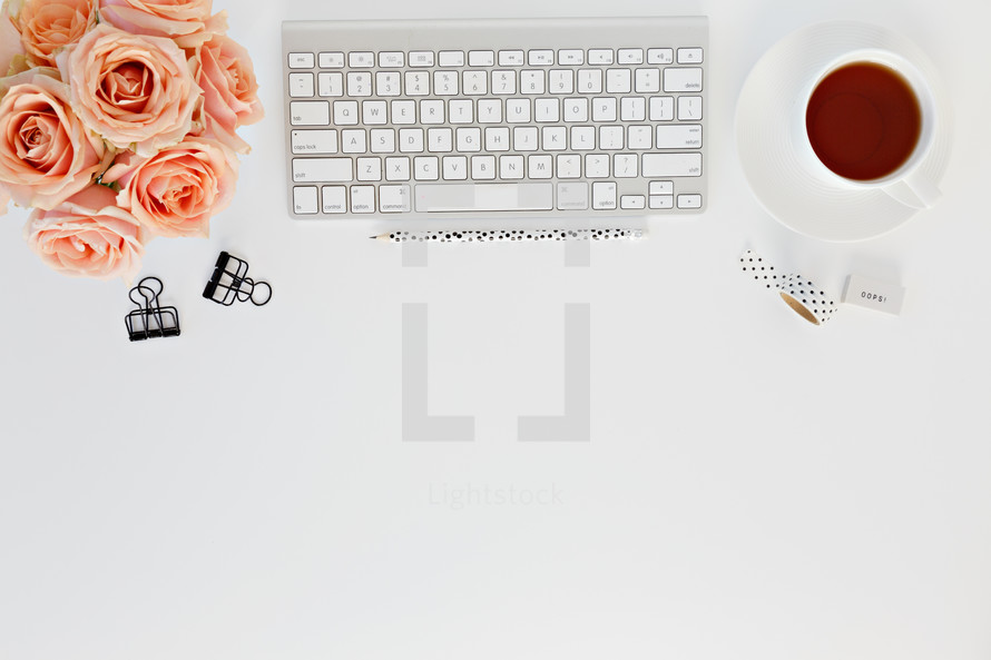 clips, computer keyboard, pencils, tea cup, and peach roses on a desk