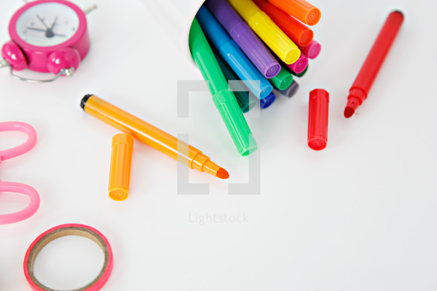 alarm clock, scissors, markers, and paperclips on a white background