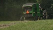 a farmer driving a bailing tractor