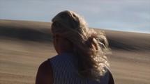 a woman walking up sand dunes in a desert