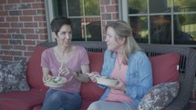 women sitting on a porch talking