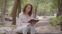 a woman reading a Bible in the park