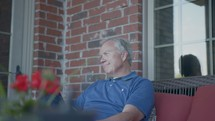 a man sitting quietly on a porch