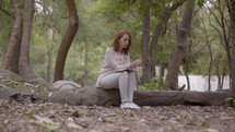 a woman praying and reading a Bible in a park