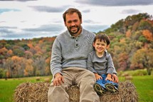 father sitting with his son on a bale of hay