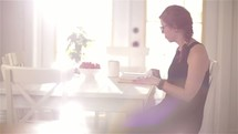 woman sitting at a kitchen table reading a Bible