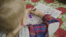 a child coloring a Christmas coloring page