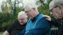 senior men praying on a park bench