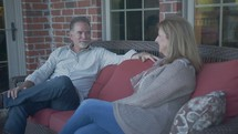 a husband and wife talking on a porch