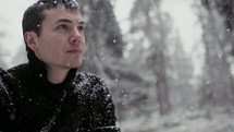 a man sitting on a rock in a forest in the falling snow
