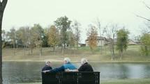 elderly men sitting on a park bench