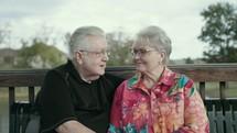 elderly couple talking outdoors