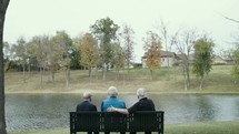 senior men talking on a park bench