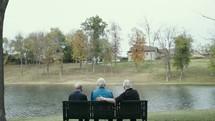senior men talking on a park bench