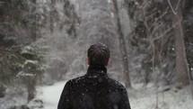 a man walking in a forest in falling snow