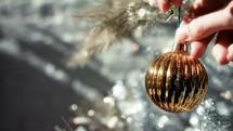 hanging a Christmas ball on a Christmas tree