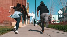 a girl and guy racing down a sidewalk in a city