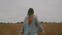 a woman walking through a field of tall grasses