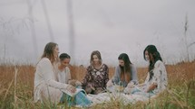 a women's group Bible study on a blanket in a field