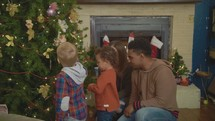 a family decorating a Christmas village display