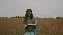 a woman walking through a field of tall grasses reading a Bible