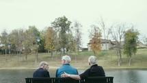 elderly men sitting on a park bench talking