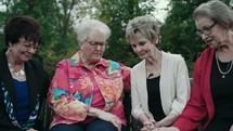 women praying sitting on a park bench