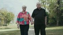 senior couple walking holding hands