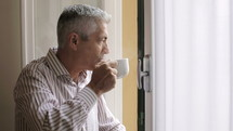 man looking out a window and drinking coffee