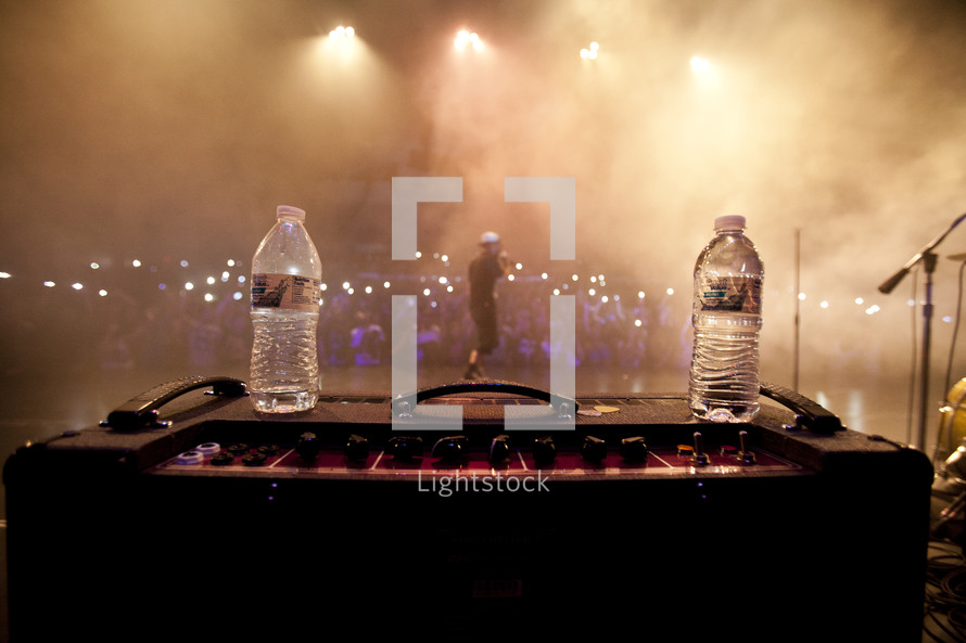 Man performing on stage behind two water bottles on an amp.