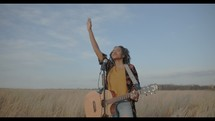 a woman with a guitar standing in a field with her arm raised
