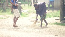 elderly woman sweeping a dirt road in Papua New Guinea