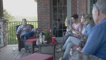 men and women sitting on a porch talking