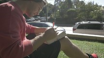 a man sitting in a park reading a Bible